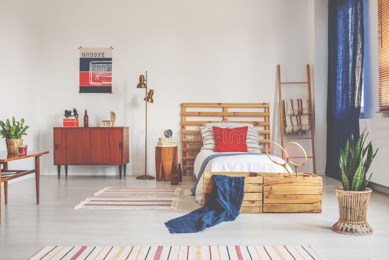 与白色卧具的木床和红色枕头在有镶边地毯和减速火箭的家具的,真正的照片宽敞卧室 图库摄影