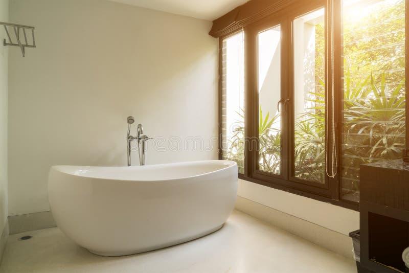 与白色卵形浴缸的现代卫生间内部 免版税库存图片