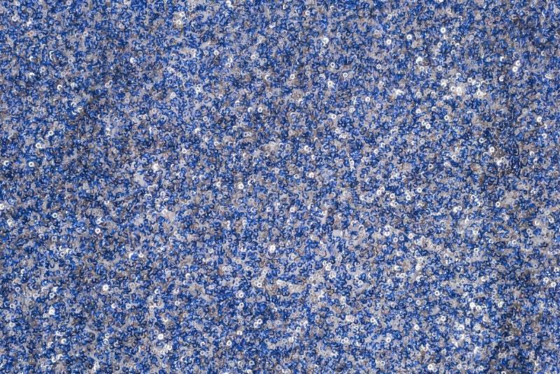 与白色和蓝色衣服饰物之小金属片的织品纹理 特写镜头 免版税库存图片