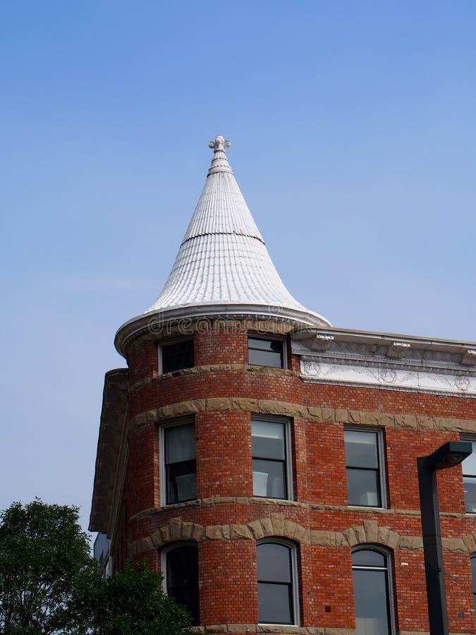 与白色圆锥形屋顶的红砖大厦 库存照片