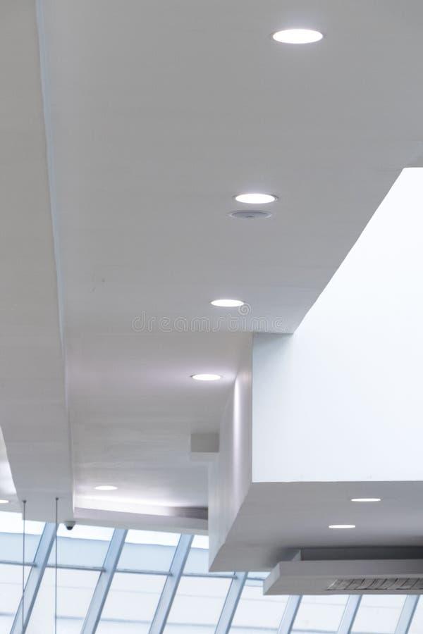 与白色圆incrustrated光和窗口的不对称的白色天花板 图库摄影