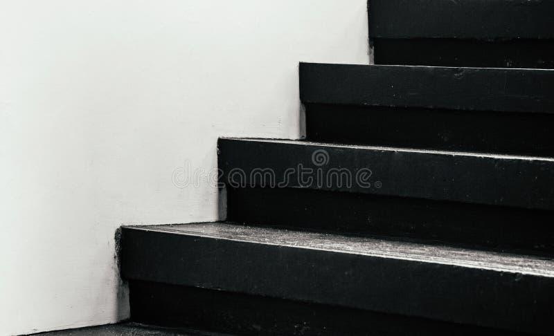 与白色墙壁的黑楼梯步-暗影单调图象 免版税库存照片