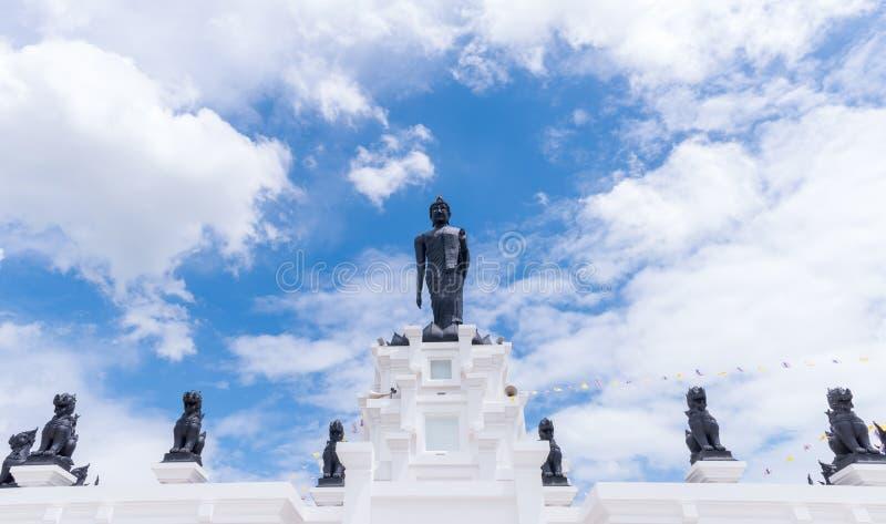 与白色多云和蓝天的黑大菩萨雕象 免版税图库摄影