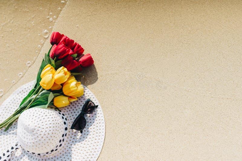 与白色太阳帽子的郁金香,黄色和红色浆糊有黑太阳镜的 库存图片