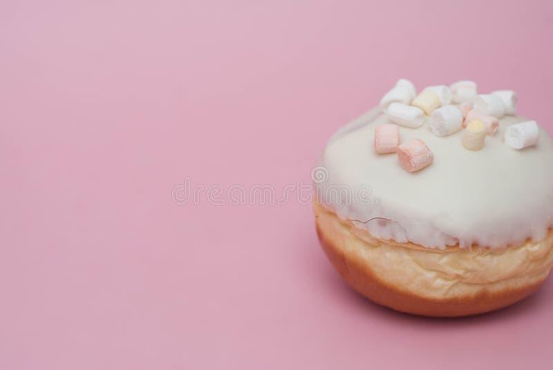 与白色奶油的多福饼在桃红色背景 与拷贝空间的甜点和点心多福饼 免版税库存图片