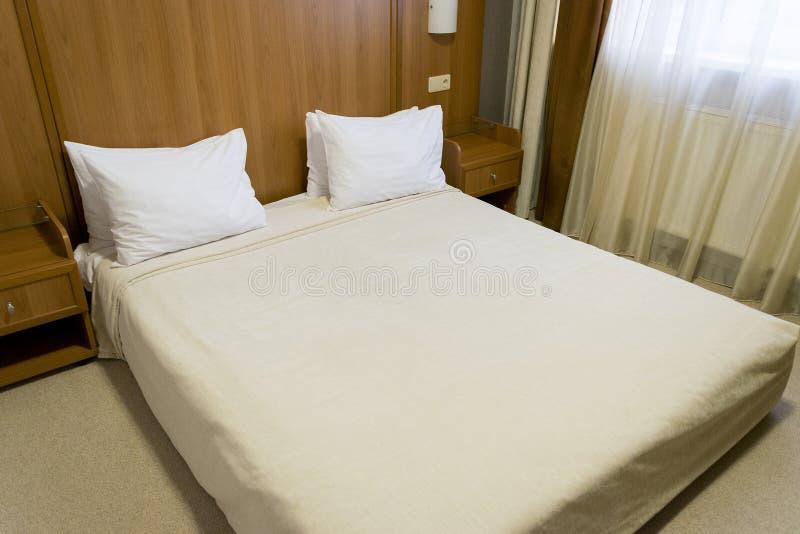 与白色床罩和枕头,木床头板的舒适的床 与木元素的现代卧室内部 免版税库存图片