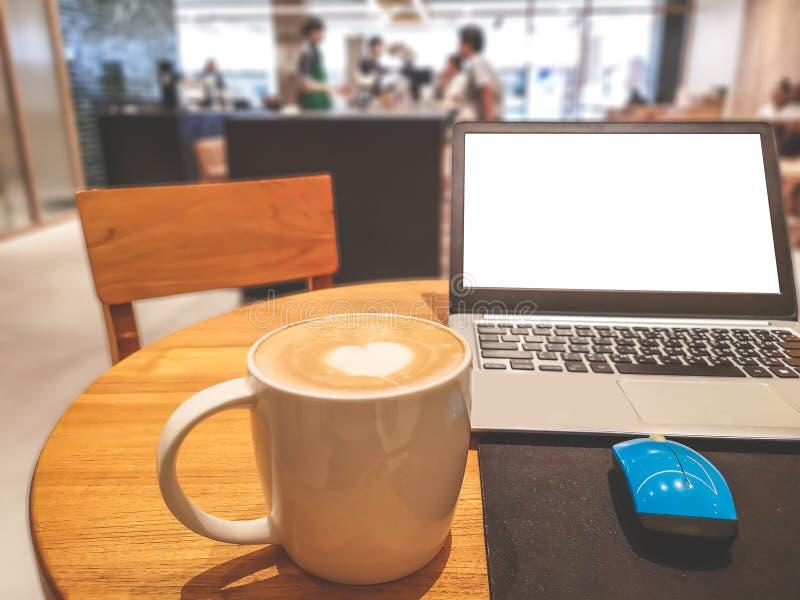 与白色心脏杯子的一白色杯子热的capuccino在上面、一白色屏幕计算机labtop和蓝色老鼠在棕色木桌上 库存图片