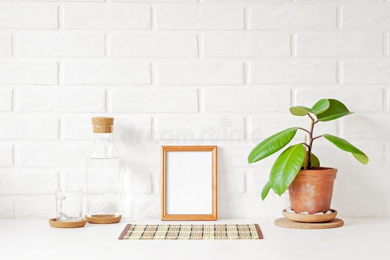 与白色拷贝空间的一个空的木画框在桌上 库存图片