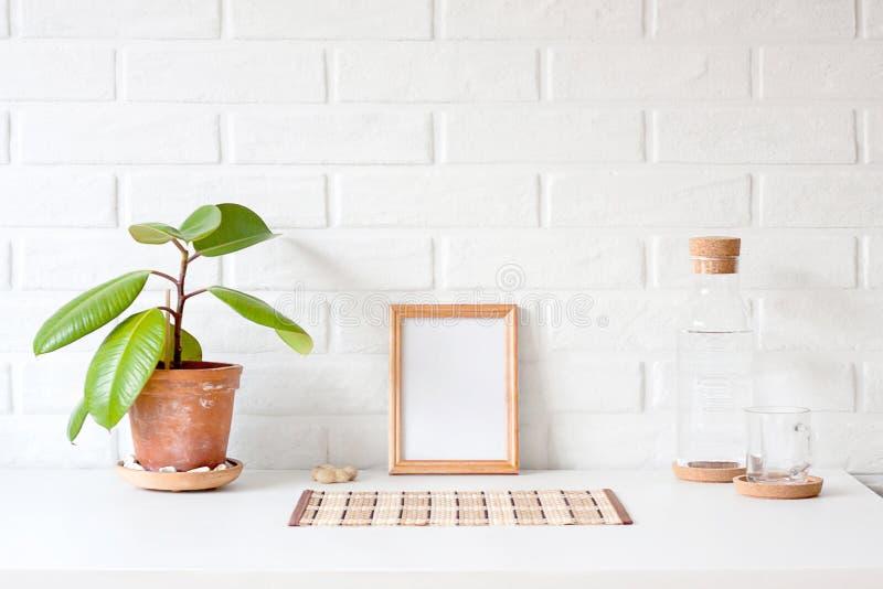 与白色拷贝空间的一个空的木画框在桌wi 库存照片