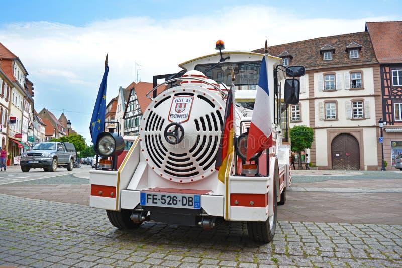 与白色旅游微型火车的边界游览塑造了有德国和法国旗子的汽车在前面,站立在集市广场 库存照片