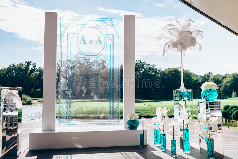 与白色日工和兰花花束的婚礼曲拱开花 库存照片