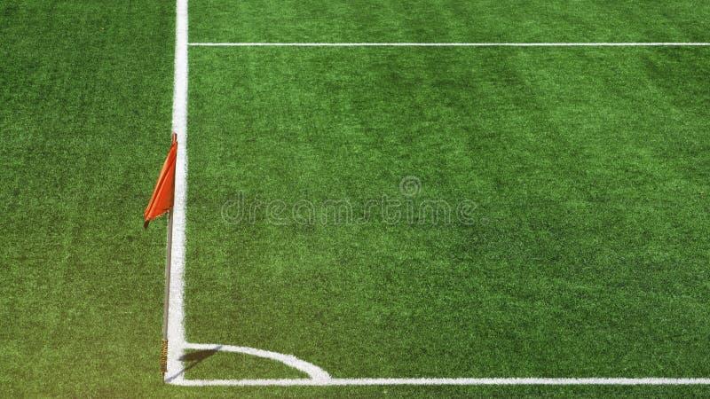 与白色条纹线的侧向红色旗杆在橄榄球场的美好的绿草橄榄球场角落 概念为 库存图片