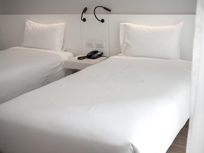 与白色枕头的白色干净的成对床在旅馆卧室 库存图片