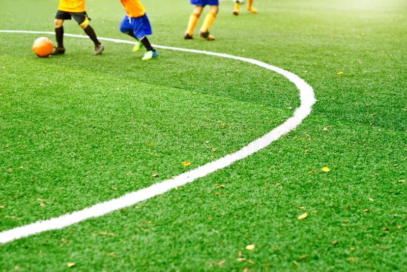 与白色标记线的绿色足球场草和男孩演奏橄榄球背景 库存图片