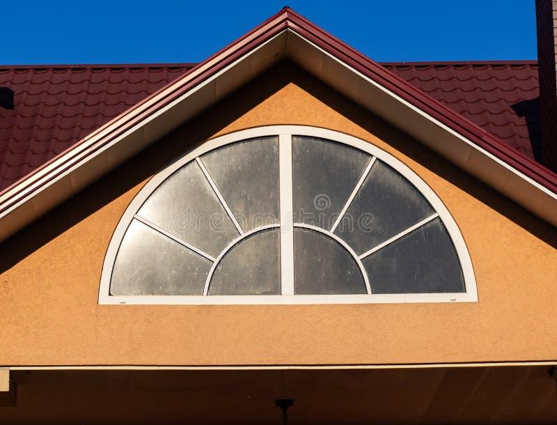 与白色框架,关闭的被成拱形的窗口,房子外部 免版税库存照片