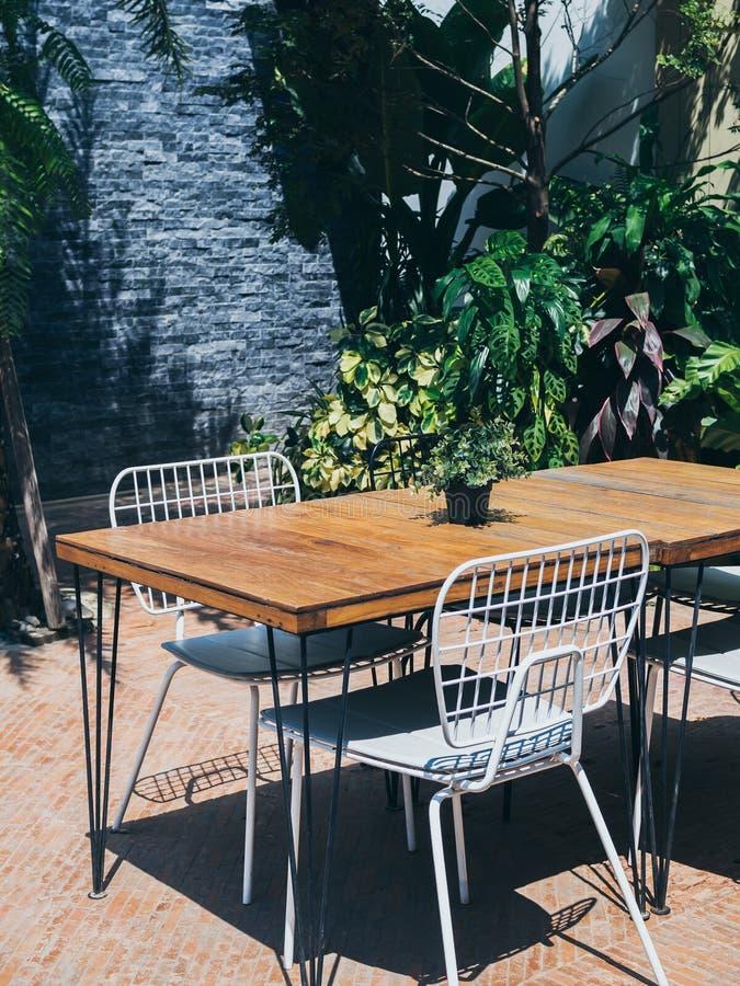 与白色椅子的木饭桌在室外庭院里 免版税库存图片