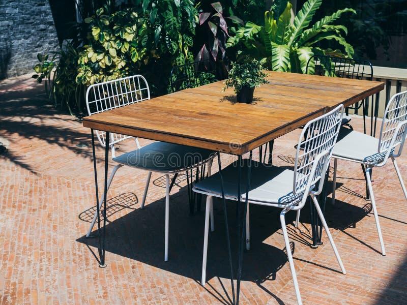 与白色椅子的木饭桌在室外庭院里 免版税库存照片