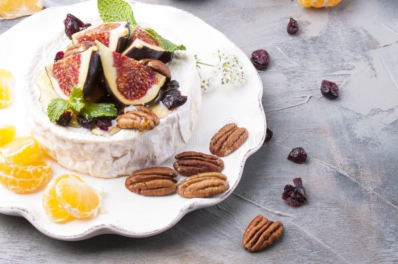 与白色模子的乳酪和无花果、蜂蜜和坚果 秋天甜点和果子和酒 晚餐的可口食物 顶视图 库存图片