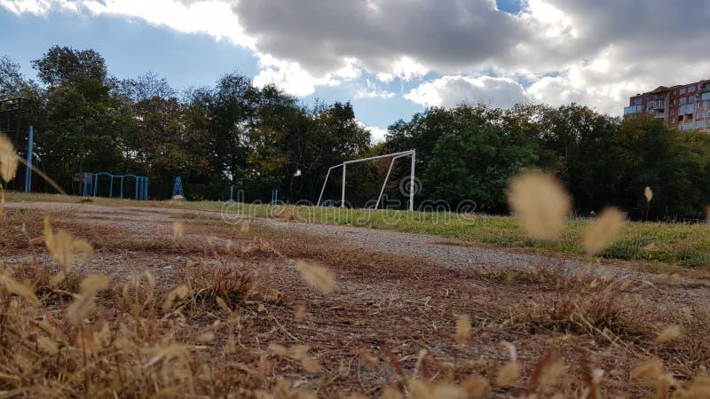 与白色橄榄球门的绿色足球场 库存图片