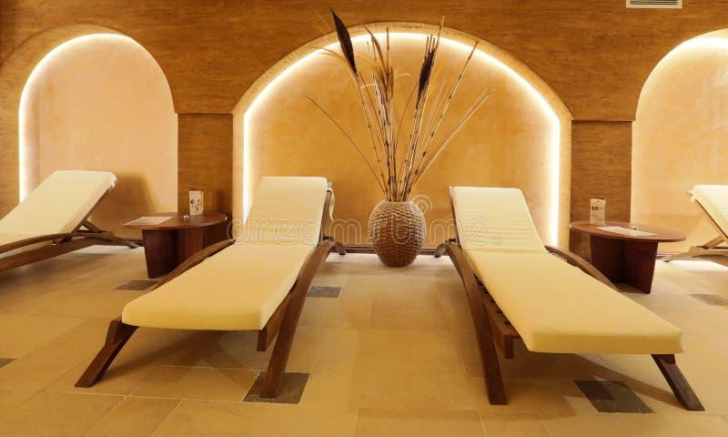 与白色毛巾的温泉休息室内部和木床 免版税库存照片