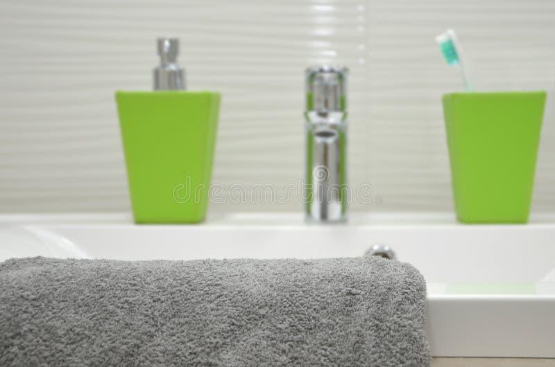 与白色水槽、银色轻拍和一块灰色毛巾的背景在前景 库存图片