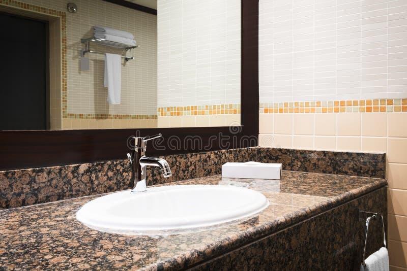 与白色水槽现代样式龙头,白色towes,石大理石桌的卫生间豪华经典红木内部 库存图片