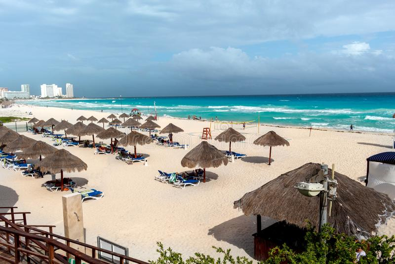 与白色沙子、绿松石海、棕榈树、小屋和多云天空的加勒比海滩 免版税库存图片