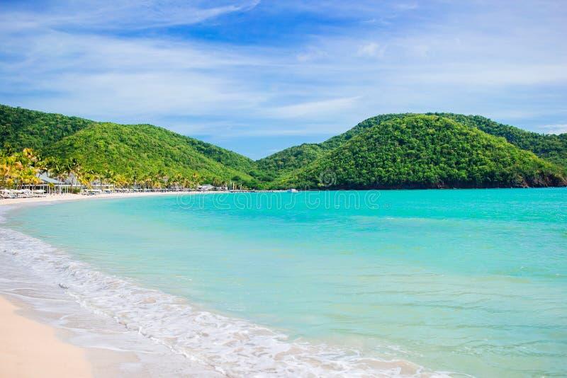 与白色沙子、绿松石海洋水和蓝天的田园诗热带卡来尔海湾海滩在安提瓜岛海岛 库存照片