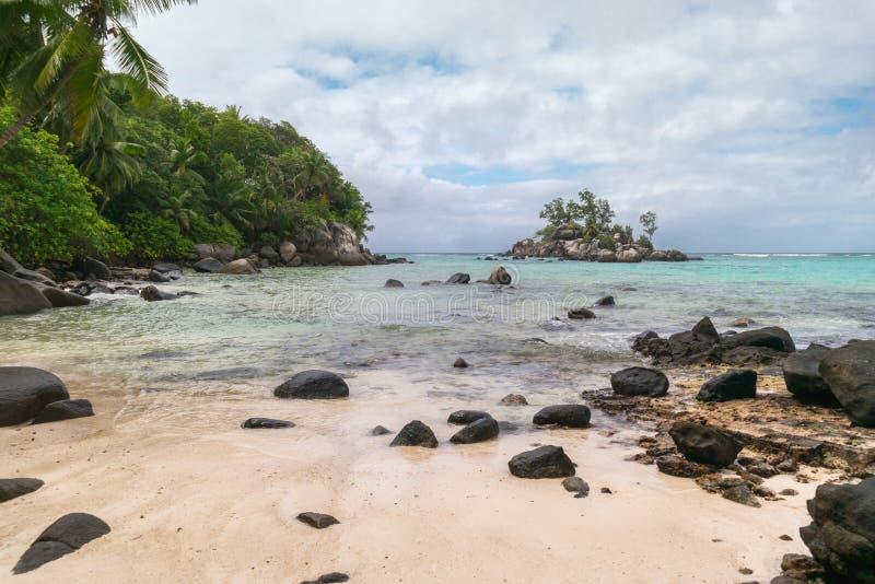 与白色沙子的平静的海湾,阴暗天空、花岗岩石头和绿松石海仙境的靠岸,塞舌尔群岛非洲 免版税库存照片
