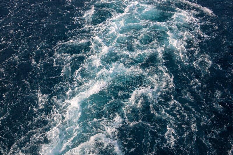 与白色泡沫似的波浪的海水纹理 热带跳岛战术或海洋旅行横幅 汽艇足迹 免版税库存照片