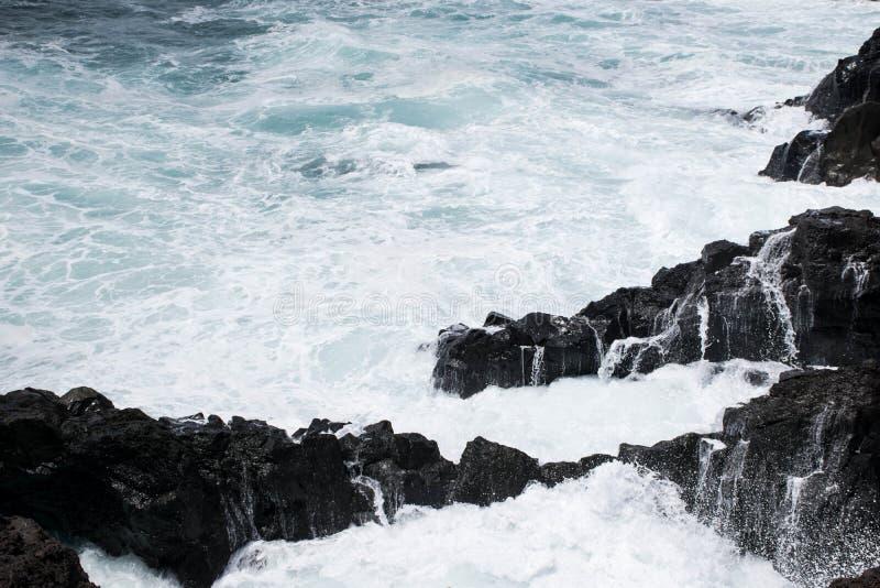 与白色泡沫海的黑熔岩岩石岸 库存照片