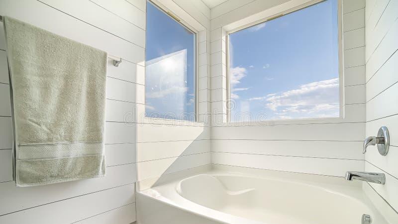 与白色浴缸和白色墙壁的全景框架最低纲领派卫生间室内设计 库存照片