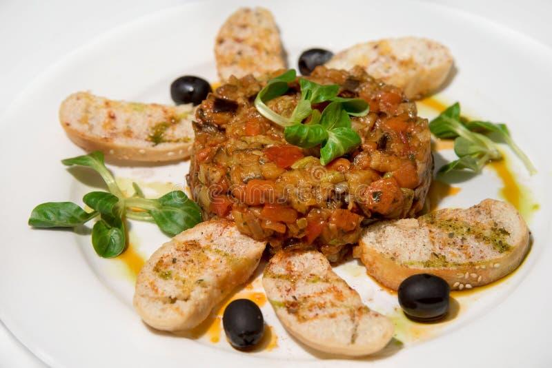 与白色烤面包片和橄榄的菜炖煮的食物在一块白色板材 库存照片