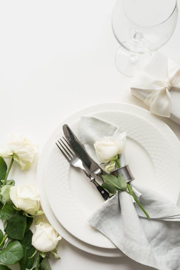 与白色玫瑰,礼物,餐具,在白色桌上的银器的浪漫和婚姻的桌设置 o 库存图片