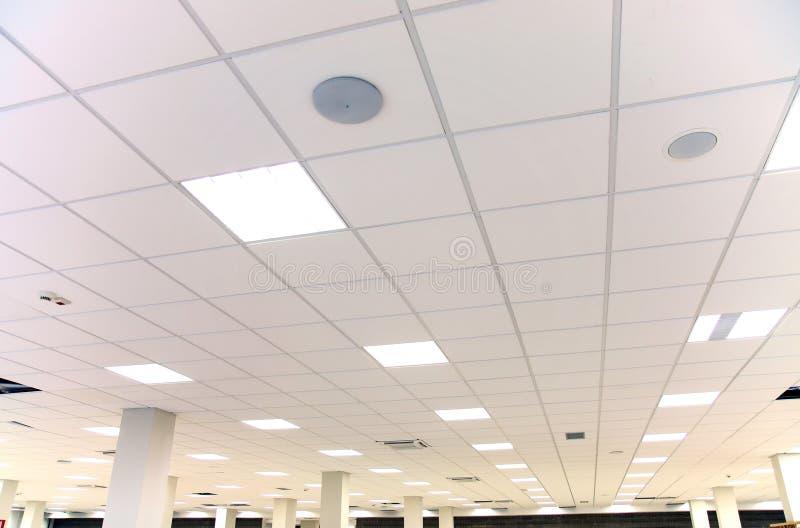 与白色瓦片和照明设备的白色办公室天花板 库存照片