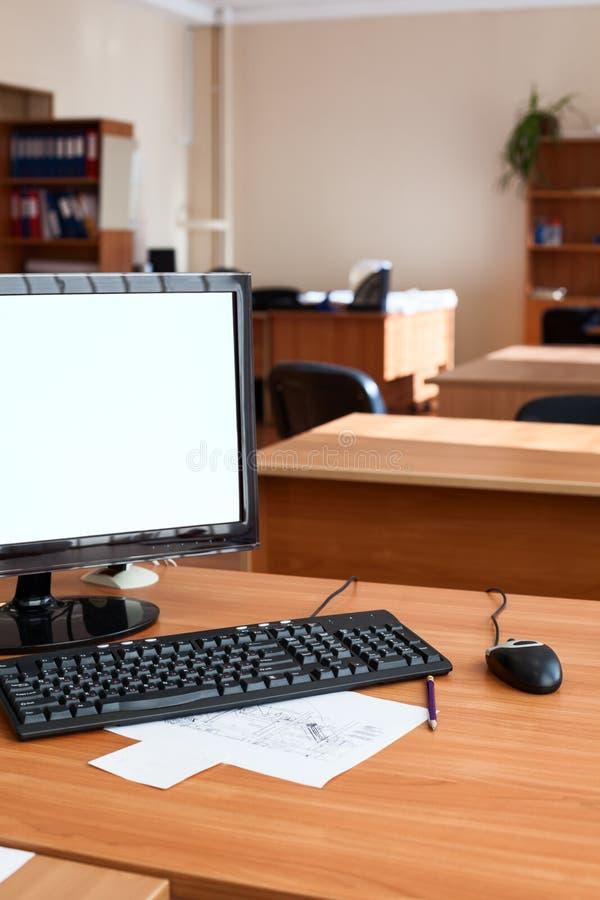 与白色的平的lcd个人计算机计算机显示器隔绝了屏幕,空的办公室室 免版税库存照片