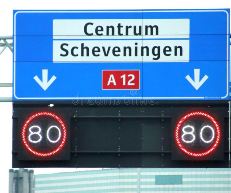 与白色的方向标对中心的地方目的地的和斯海弗宁恩和必须的在它下限速在t的高速公路A12 免版税库存图片
