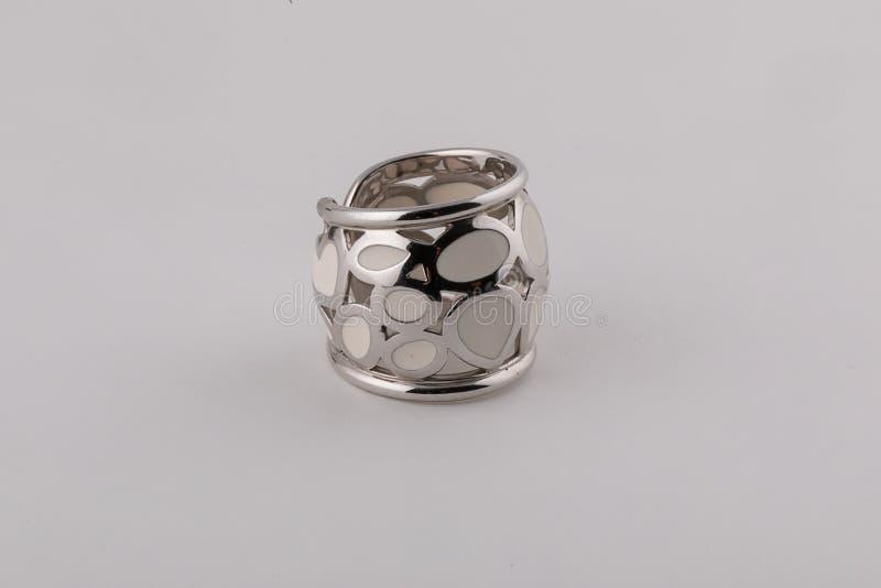 与白色石头的女性银色对此的圆环和图在白色背景 免版税库存照片
