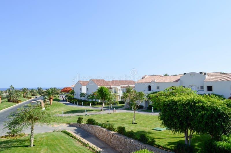 与白色石房子的美好的热带手段有红色瓦片、棕榈树、异乎寻常的植物和绿草屋顶的反对b 免版税库存照片