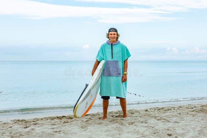与白色空白的水橇板的英俊的人步行等待波浪冲浪斑点在海海洋岸 体育的概念 库存图片