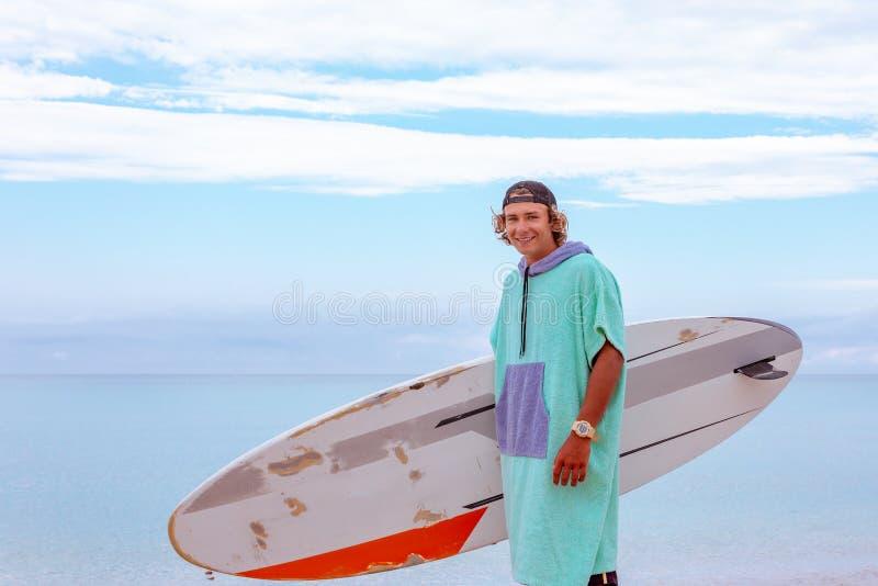 与白色空白的水橇板的英俊的人步行等待波浪冲浪斑点在海海洋岸 体育的概念 库存照片