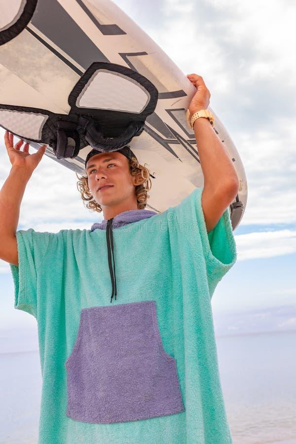 与白色空白的水橇板的英俊的人步行等待波浪冲浪斑点在海海洋岸 体育的概念 免版税图库摄影