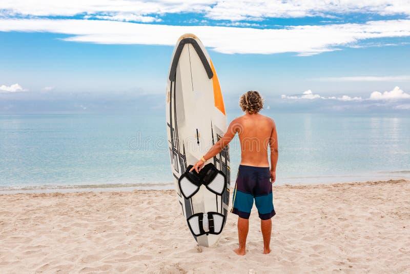 与白色空白的水橇板的英俊的人步行等待波浪冲浪斑点在海海洋岸 体育的概念 免版税库存照片