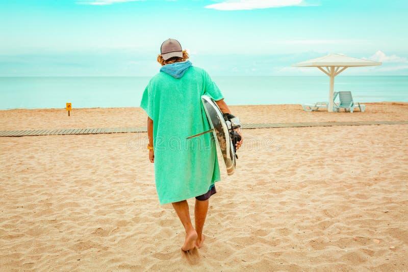 与白色空白的水橇板的英俊的人步行等待波浪冲浪斑点在海海洋岸 回到视图 概念  图库摄影