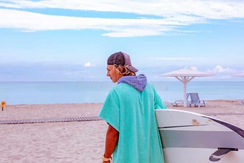 与白色空白的水橇板的英俊的人步行等待波浪冲浪斑点在海海洋岸 回到视图 概念  免版税库存照片