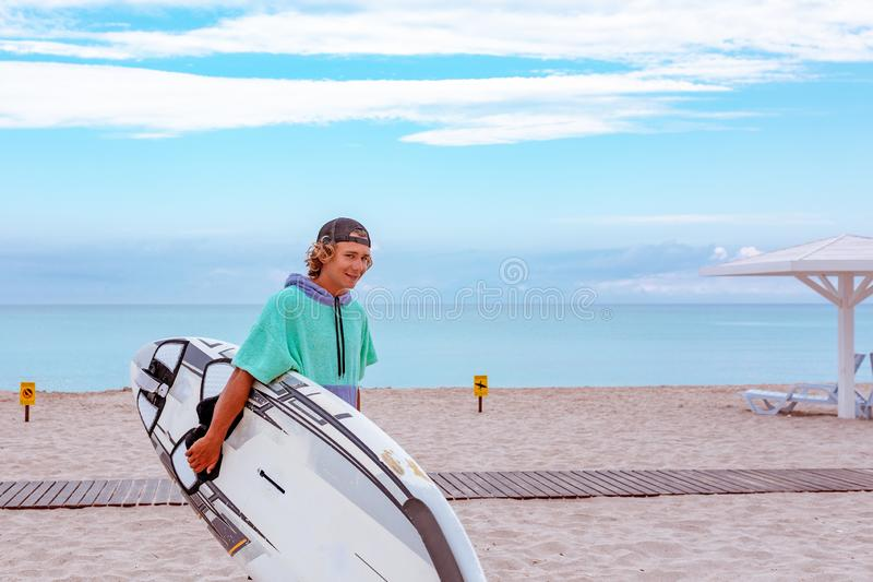 与白色空白的水橇板的英俊的人步行等待波浪冲浪斑点在海海洋岸 看从旁边 概念 免版税库存照片