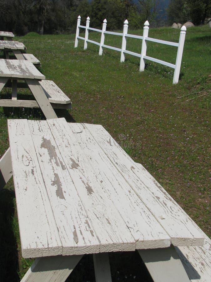 与白色篱芭的退色的野餐桌在背景中 免版税图库摄影
