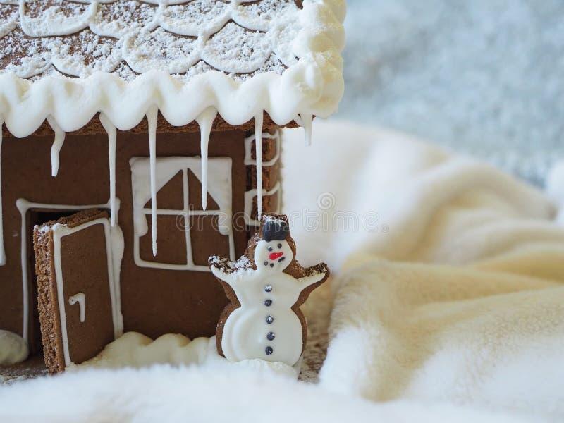 与白色结冰的姜饼雪人在华而不实的屋前面 免版税库存照片