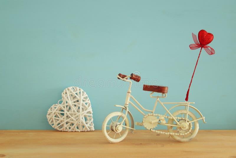 与白色葡萄酒自行车玩具的情人节浪漫背景和对此的闪烁红色心脏在木桌 免版税库存图片