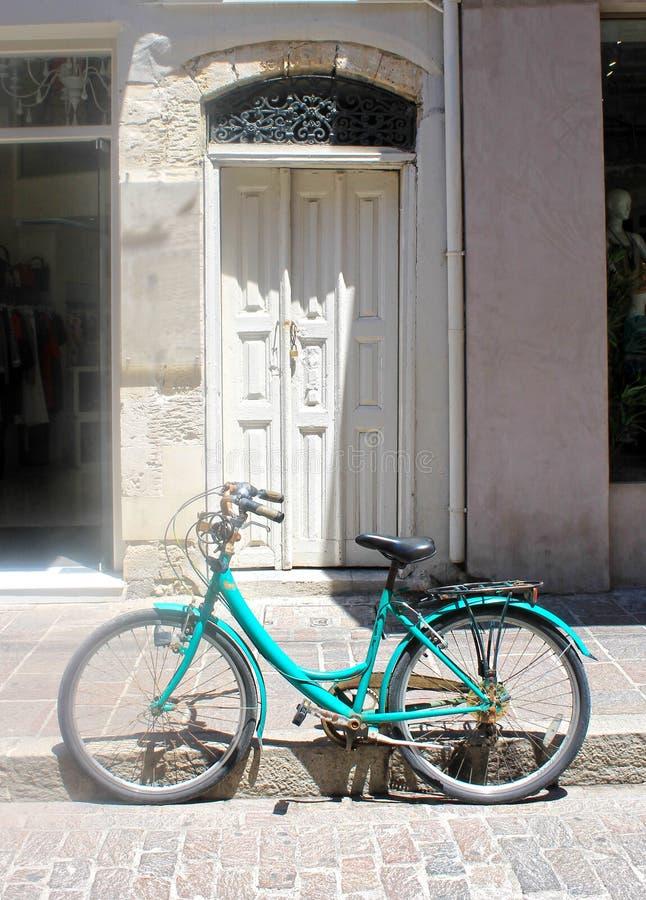 与白色门和葡萄酒的老大厦停放了自行车,希腊 库存图片